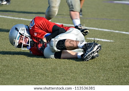 CUMMING, GA/USA - SEPTEMBER 22: Unidentified boy falling on the football after a pass. Two teams of 7th grade boys September 22, 2012 in Cumming GA. North Forsyth vs Lakeside. - stock photo