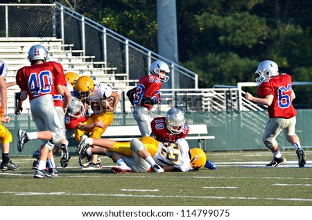 CUMMING, GA/USA - SEPTEMBER 22: Unidentified players  tackling the ball carrier during a football game of 7th grade boys September 22, 2012 in Cumming GA. North Forsyth vs Lakeside. - stock photo