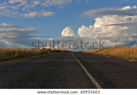 Cumulo-nimbus clouds building up over a road on the South African countryside near Machadodorp - stock photo