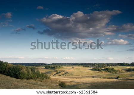 Cumulus clouds over a village - stock photo