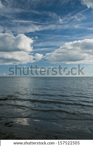 Cumulus clouds over the lake - stock photo