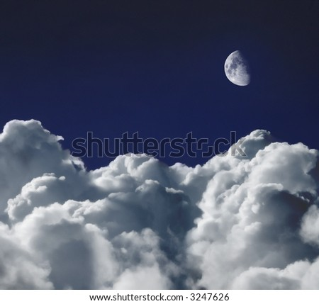 Cumulus clouds shot from a high altitude against an indigo blue sky with the moon above