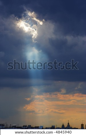 Cumulus clouds with sun rays - God looks down at earth. - stock photo