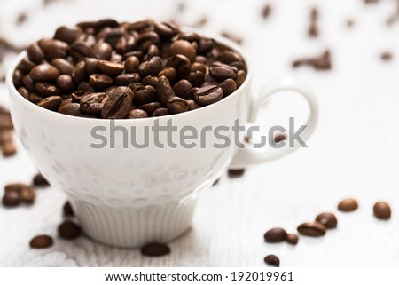 Cup and coffee beans on white wooden surface
