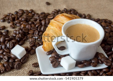 Cup and grain of coffee over textile background