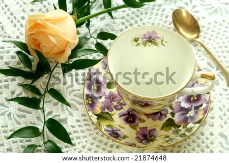Cup and rose on knitted table cover