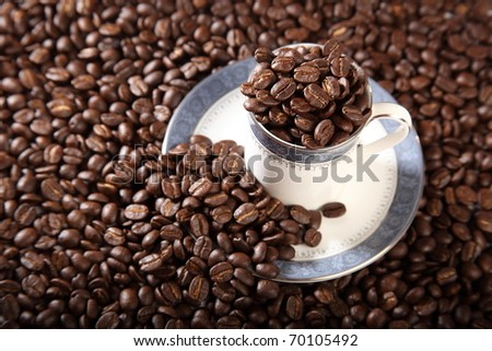 Cup and saucer full of roasted coffee beans - stock photo