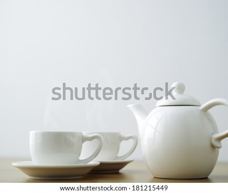 cup and saucer with teapot on table.