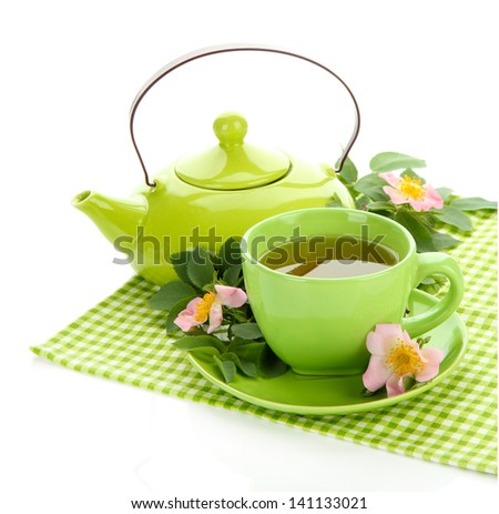 Cup and teapot of herbal tea with hip rose flowers, isolated on white - stock photo