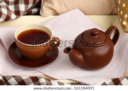 Cup and teapot on tray on bed close up