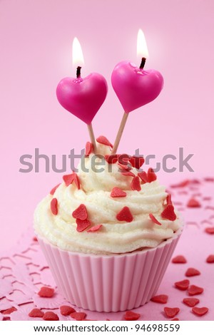 Cup cake with heart candles on pink background - stock photo