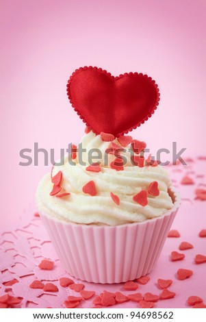 Cup cake with heart shaped decoration on pink background - stock photo