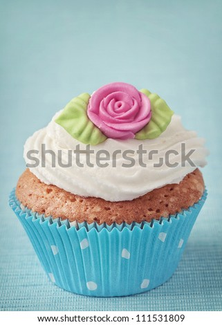 Cup cake with pink marzipan rose - stock photo