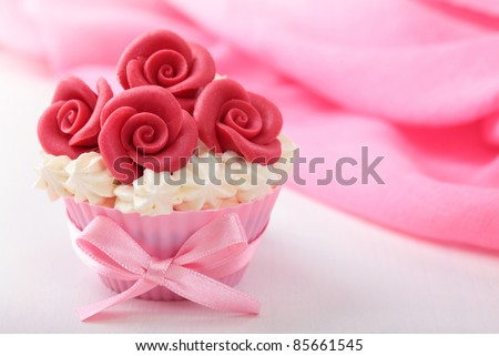 Cup cake with red marzipan roses - stock photo
