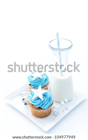 Cup cakes with blue frosting, silver ribbons and a glass bottle of fresh milk - stock photo