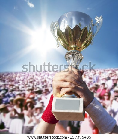 Cup for the first place in hands of the champion.  - stock photo