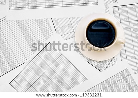 Cup from coffee on documents. - stock photo