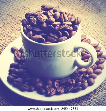 Cup full of coffee beans.  Instagram style filtred image - stock photo