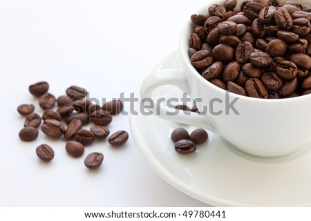Cup full of coffee beans on a white background