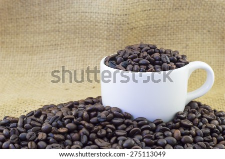 Cup full of coffee beans on burlap hessian sacking texture background - stock photo