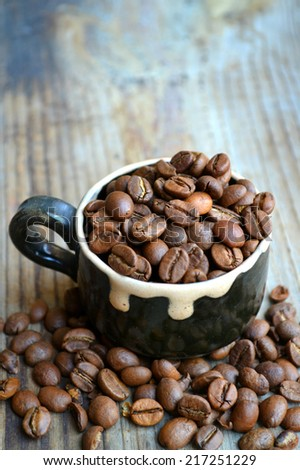 Cup full of coffee beans on wooden table - stock photo