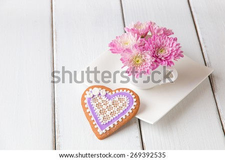 Cup full of pink  mum flowers and  heart shape cookie on white wooden table. - stock photo