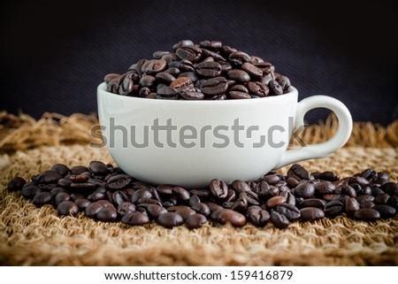 cup full of roasted coffee beans