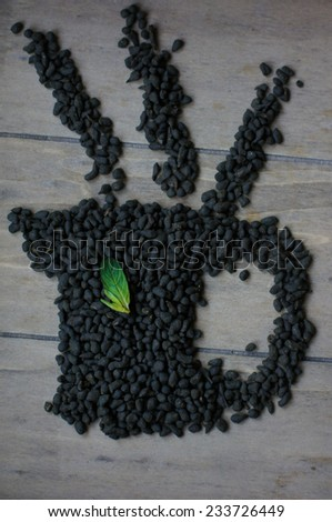 Cup made from tea leaf on wooden background - stock photo