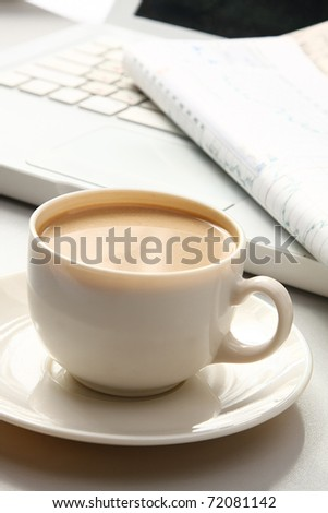 cup near the laptop - stock photo