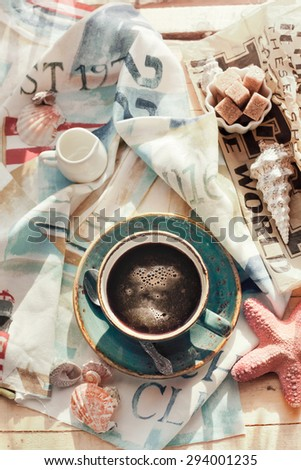 Cup of americano coffee set with seashells, milk and sugar on marine themed napkin. Holiday by tropical sea relaxation concept. Brightly sunlit setting, natural light. Toned photo. - stock photo