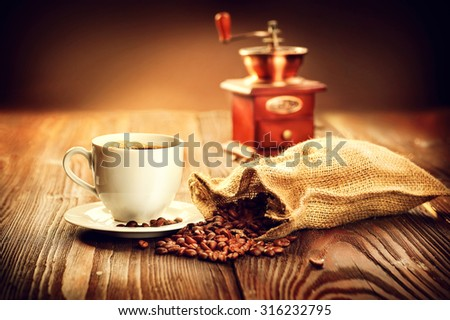 Cup of aromatic coffee on saucer with burlap sack full of roasted coffee beans and coffee grinder on wooden table. Cup of warm coffee with bag with coffee grain over vintage wooden background - stock photo