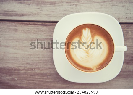 Cup of art latte or cappuccino coffee with retro filter effect - stock photo