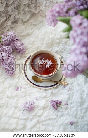 Cup of black aroma tea with lilac flowers on white textile background - stock photo