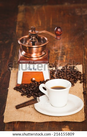 Cup of black coffee and a cigar in the background grinder on a wooden rustic table - stock photo