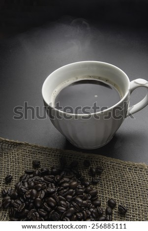 Cup of black coffee and beans/Coffee beans and coffee/Black coffee with dark beans on burlap - stock photo