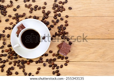 Cup of black coffee, chocolate and coffee beans on a wooden background, place for text - stock photo