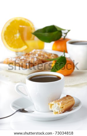 Cup of black coffee, eclairs, juice and fruit.