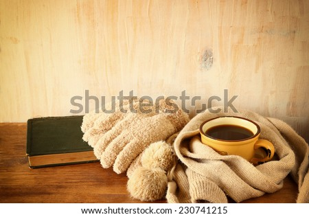 Cup of black coffee with  a warm scarf and old book on wooden background. filtered image - stock photo