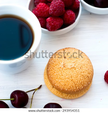 cup of black strong coffee and two biscuits with berries - raspberries and cherries, summer light breakfast