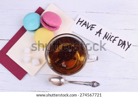 """Cup of black tea on the table. Tea, three macaroones and a note """"Have a Nice Day"""". Breakfast, lunch. Dessert, sweet, sweet tooth. Cup, tea spoon, sugar cubes, macaroon and banner. Note wish. - stock photo"""