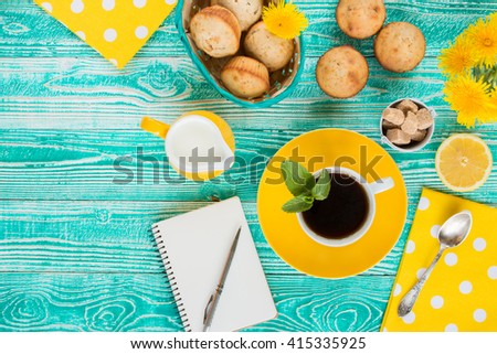 cup of black tea on yellow plate and yellow milk jug cane sugar, notebook, pen, cakes, dandelions, teaspoon on turquoise colored wooden table with yellow napkin at polka dots top view