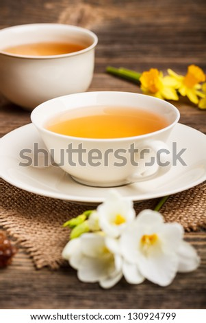 Cup of black tea with freesia flowers