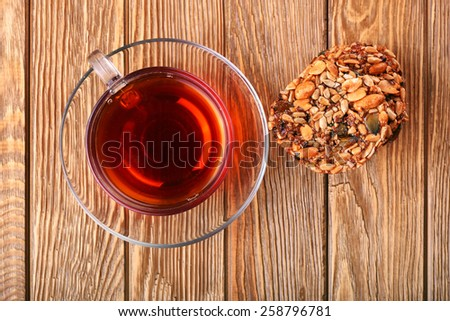 Cup of brown tea and healthy cereals seed cookies on wooden table background top view - stock photo