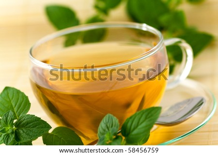 Cup of brown tea on the saucer with mint