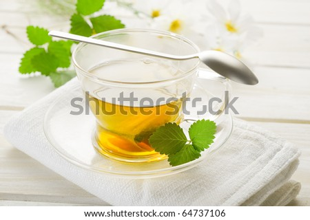 cup of camomile with leaf and flower - stock photo
