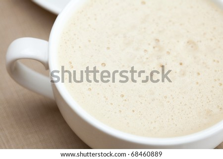 cup of cappuccino, a piece of cake with nuts lying on the plate - stock photo