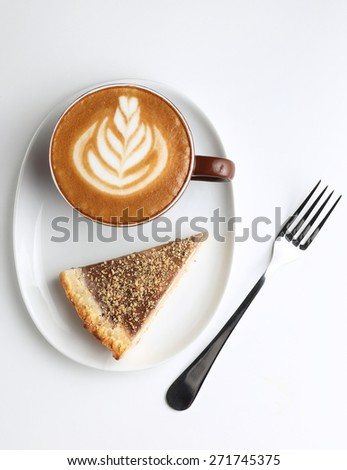 Cup of cappuccino and a piece of cake. Latte art. Isolated on white. Top view - stock photo