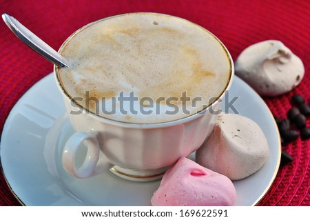 Cup of cappuccino and meringue cookies