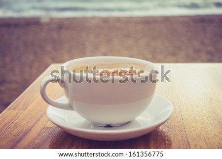 Cup of cappuccino by the sea - stock photo