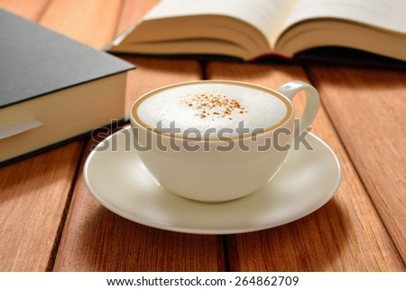 Cup of cappuccino coffee and books on wooden table - stock photo